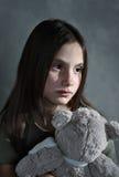 Droevig jong meisje met stuk speelgoed Stock Afbeeldingen