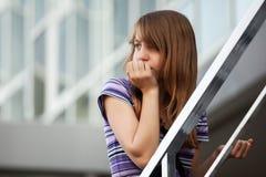 Droevig jong meisje tegen een schoolgebouw Stock Foto's