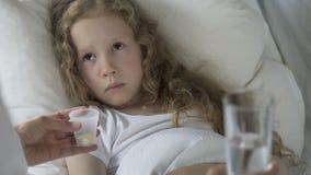 Droevig Kaukasisch kind die in bed liggen en pillen in de handen van de arts, ziekte bekijken stock video