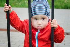 Droevig kijkt weinig jongen door een rooster Stock Afbeelding
