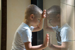 Droevig kind dichtbij venster Stock Afbeelding