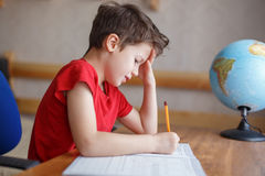 Droevig kind die aan hard thuiswerk thuis werken royalty-vrije stock foto