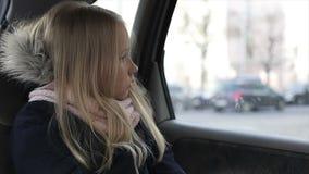 Droevig kind die aan het autoraam kijken Weinig blondemeisje op achterbank in auto stock footage