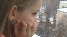 Droevig Kind die op Venster, Ongelukkig Nadenkend Jong geitje, Meisjesgezicht, de Sneeuwende Winter kijken royalty-vrije stock fotografie