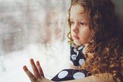Droevig kind die uit het venster kijken Stemmende foto royalty-vrije stock afbeelding