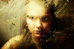 Droevig meisje achter vuil glas Stock Foto