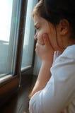 Droevig meisje dichtbij een venster Royalty-vrije Stock Afbeelding