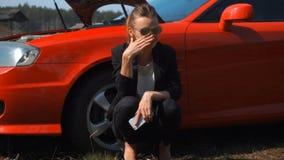 Droevig meisje dichtbij rode gebroken auto stock footage