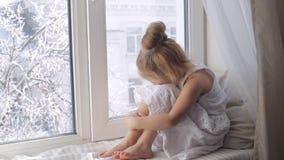 Droevig meisje die door de vensterzitting kijken op venstervensterbank De winter buiten stock footage