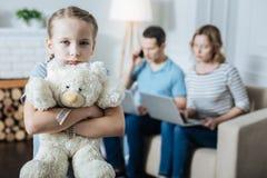 Droevig meisje die haar teddybeer koesteren stock fotografie