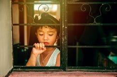 Droevig meisje die uit het venster kijken stock afbeeldingen