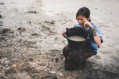 Droevig meisje die voor de regen op gebarsten droge grond bidden stock foto