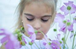 Droevig meisje en purpere bloemen stock afbeelding