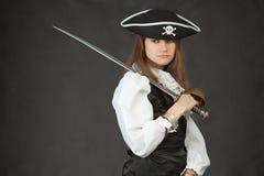 Droevig meisje in kostuum van piraat met sabel Stock Foto's
