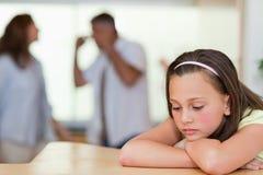 Droevig meisje met haar vechtende ouders achter haar Royalty-vrije Stock Afbeelding