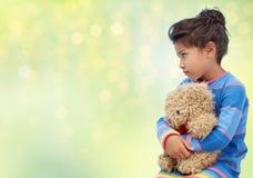 Droevig meisje met teddybeer over groene lichten stock afbeelding