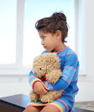 Droevig meisje met teddybeerstuk speelgoed thuis stock fotografie