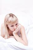 Droevig meisje op het bed stock foto's