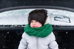 Droevig meisje in warme kleren die zich in open boomstam van auto in de winter bevinden stock fotografie