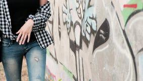 Droevig offfended meisje kijkt wispelturig terwijl het lopen en het leunen tegen de muur stock videobeelden