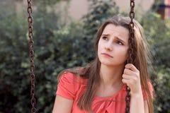 Droevig ongelukkig tienermeisje met lange donkerbruine haarzitting op een schommeling die droevig omhoog eruit zien royalty-vrije stock afbeelding