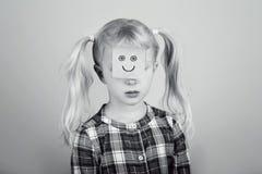 Droevig ongelukkig wit blonde Kaukasisch peutermeisje met grappig kleverig notadocument op haar gezicht stock foto's