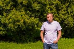 Droevig portret van een mens in een witte T-shirt die zich buiten in park bevinden stock foto