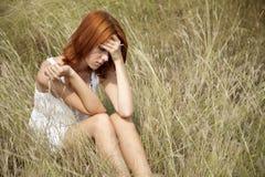 Droevig roodharig meisje bij gras. Royalty-vrije Stock Afbeeldingen
