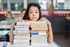 Droevig Schoolmeisje die Chin On Stacked Books At rusten Royalty-vrije Stock Afbeeldingen