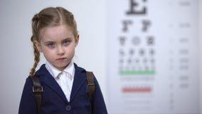 Droevig schoolmeisje die glazen, ontevreden met gezichtsproblemen opstijgen, oogziekte stock footage