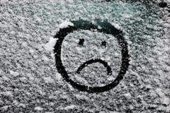 Droevig smileygezicht dat op snow-covered glas wordt getrokken Stock Fotografie