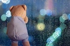 Droevig Teddy Bear die bij venster in regenachtige dag schreeuwen stock fotografie