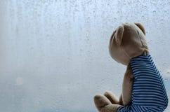 Droevig Teddy Bear-zitting en het bekijken uit het venster in regenachtige dag stock foto