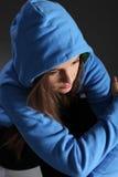 Droevig tienermeisje alleen op vloer in blauwe hoodie Stock Fotografie