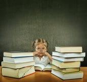 Droevig, vermoeid, bezig meisje met grote ogen, die glazen dragen die in de bank naast hem velen, vele boeken zitten Stock Foto