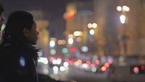 Droevig vriend en meisje die verlichte nachtstad bekijken, verbreken, strijd stock videobeelden