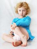 Droevig weinig blonde krullend zittingsmeisje op het wit Stock Foto's