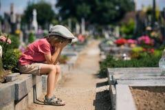 Droevig weinig jongen, die op een graf in een begraafplaats zitten, die droevig voelen stock afbeeldingen