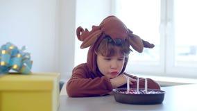 Droevig weinig jongen die in rendierkostuum zijn alleen verjaardag vieren stock footage