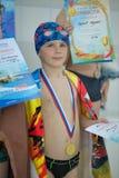 Droevig weinig jongen met een medaille voor het zwemmen royalty-vrije stock fotografie