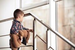 Droevig weinig jongen met stuk speelgoed op treden stock foto