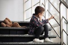 Droevig weinig jongen met stuk speelgoed zitting op treden stock afbeeldingen