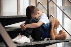 Droevig weinig jongen met stuk speelgoed zitting op treden stock afbeelding