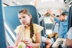droevig weinig schoolmeisje die op schoolbus berijden terwijl haar klasgenoten die hoogte vijf geven vertroebelden royalty-vrije stock foto