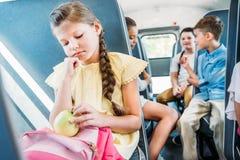 droevig weinig schoolmeisje die op schoolbus berijden terwijl haar klasgenoten die vertroebelden babbelen royalty-vrije stock afbeeldingen