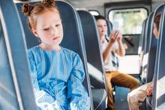 droevig weinig schoolmeisjezitting alleen in schoolbus terwijl haar klasgenoten het babbelen royalty-vrije stock afbeeldingen