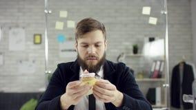 Droevige aantrekkelijke zakenman die een eenzame verjaardag in het bureau vieren, blaast hij een kaars op een kleine cake Hij is stock videobeelden