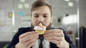 Droevige aantrekkelijke zakenman die een eenzame verjaardag in het bureau vieren, blaast hij een kaars op een kleine cake Hij is stock video