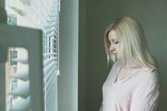 Droevige apathische eenzame vrouw die door een venster thuis of hotel, scheidings, depressie en apathieconcept kijken royalty-vrije stock fotografie