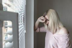 Droevige apathische eenzame vrouw die door een venster thuis of hotel, scheidings, depressie en apathieconcept kijken stock foto's